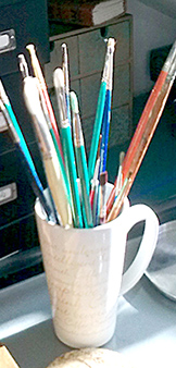 Paint brushes and pots in my studio.